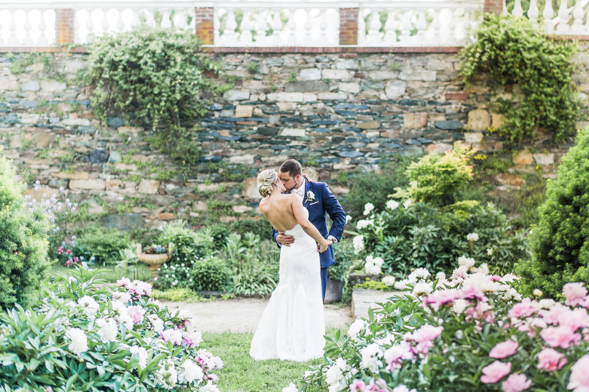 Bride and groom kissing in the middle of the peony gardens at Oatlands in Leesburg, Virginia