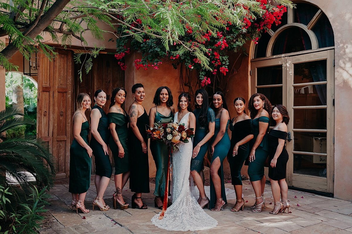 Bride holds bouquet surrounded by ten bridesmaids dressed in green in a garden courtyard