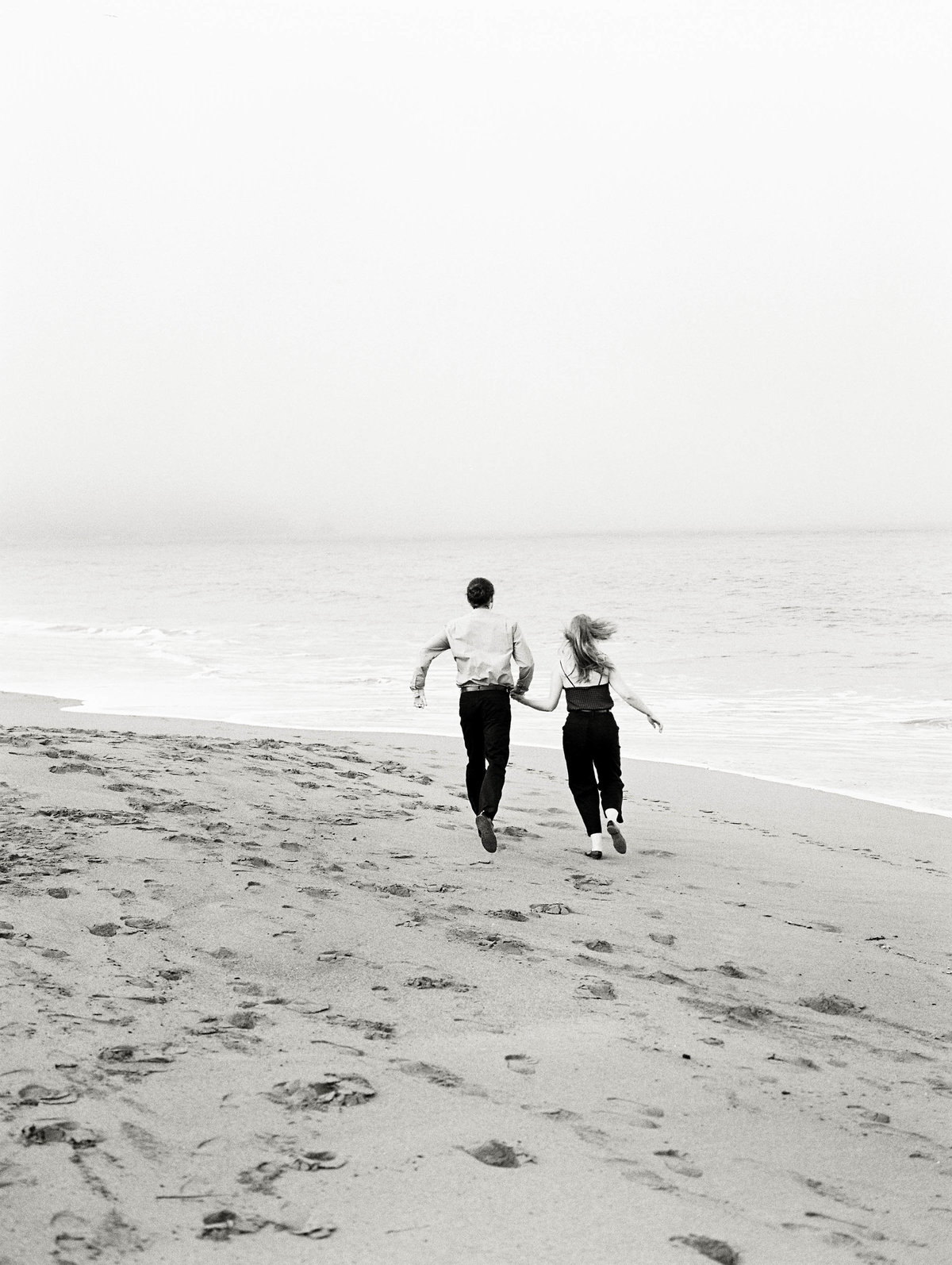 Bakers beach portrait session- couple running towards the ocean with the fog rolling in