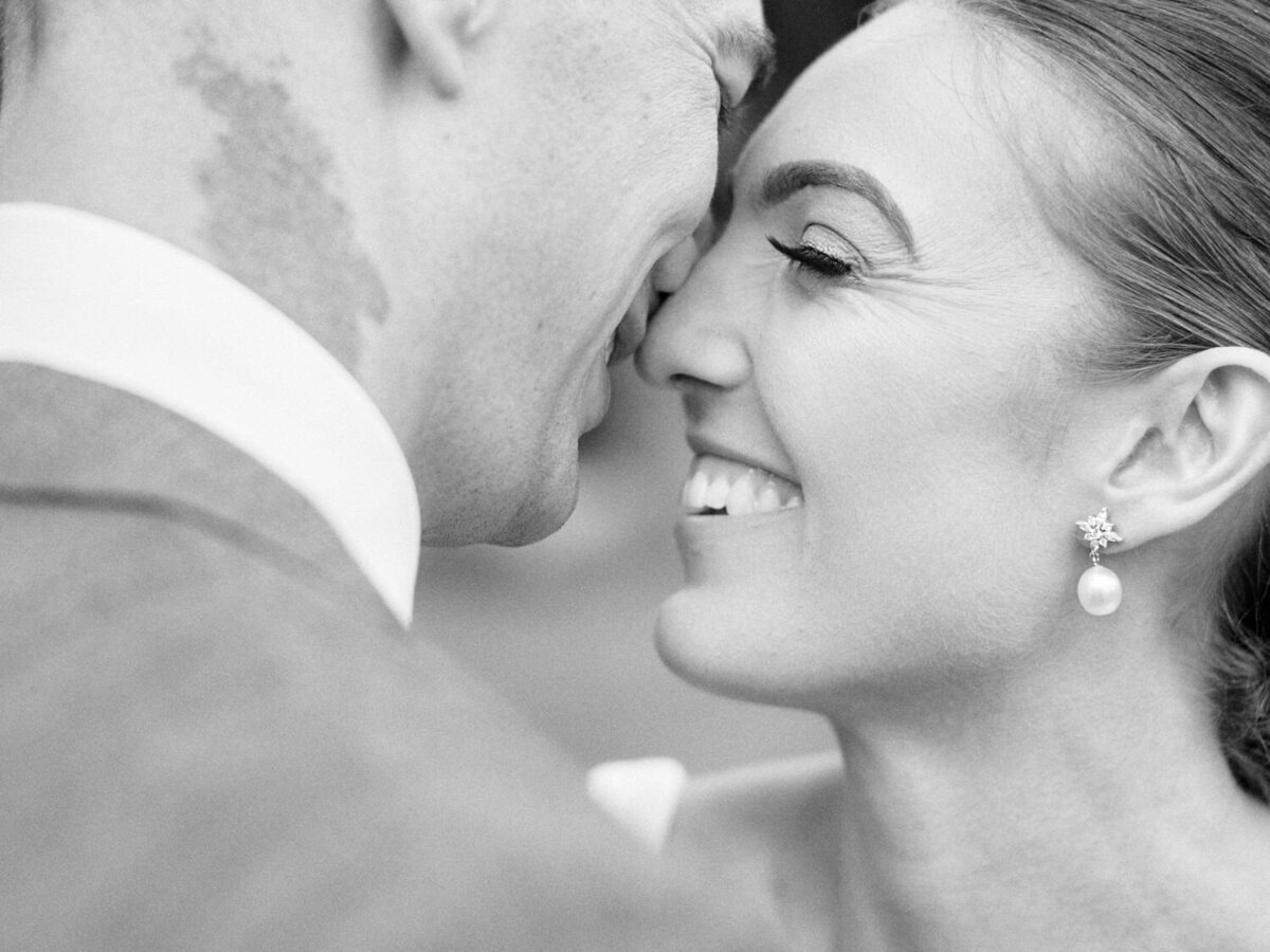 Black and white closeup of bride and groom faces smiling