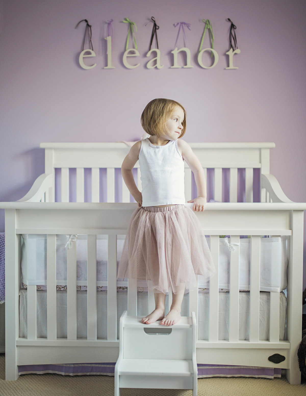 charlotte family photographer creates a beautiful lifestyle portrait of big sister standing by the new baby's crib