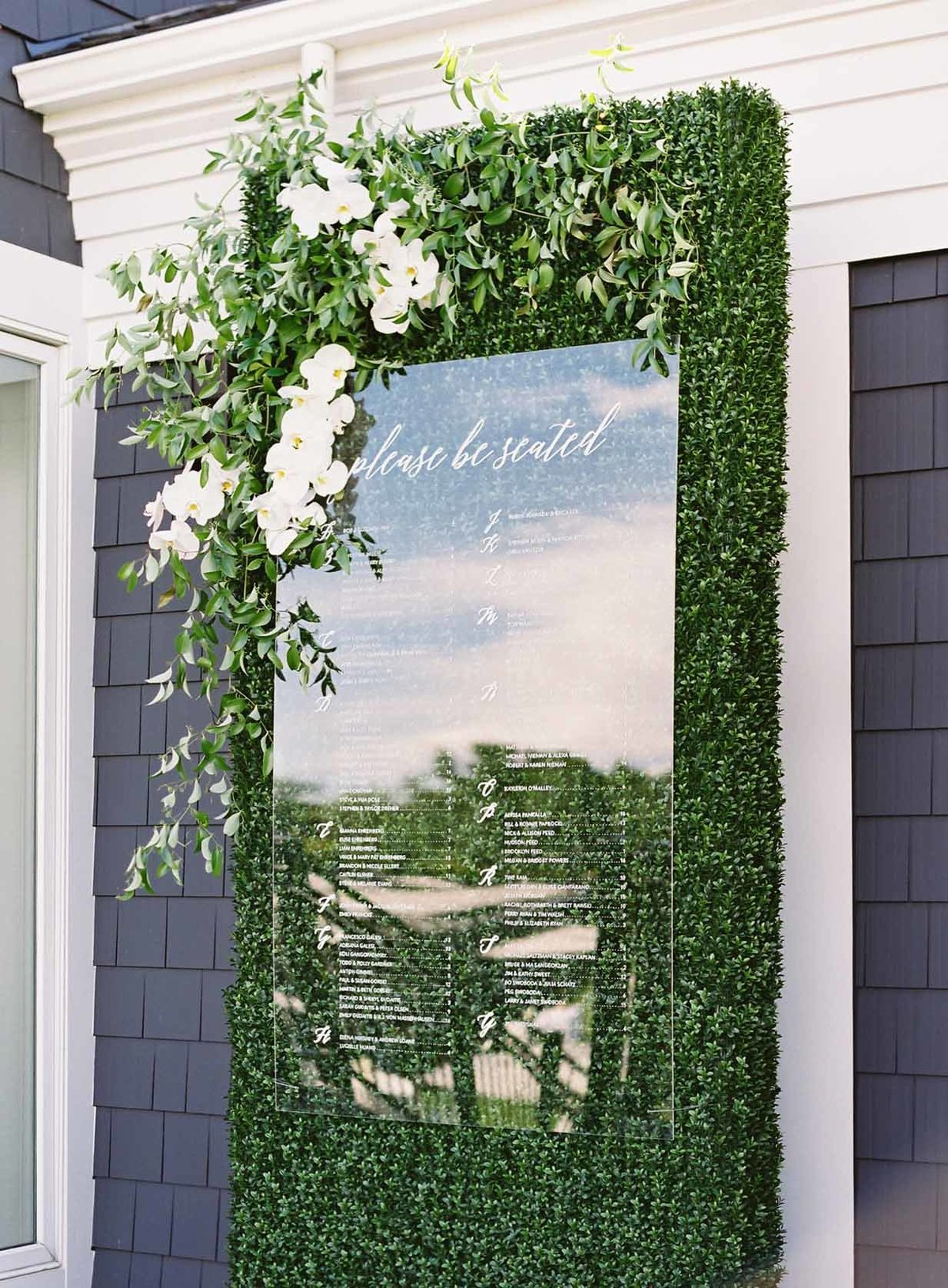 Lucite escort card board hangs on a custom green wall with white orchids
