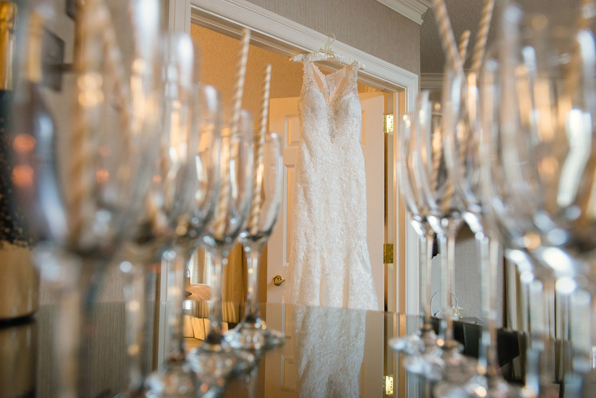 Champagne glasses and bride's dress hanging at The Inn at Fox Hollow