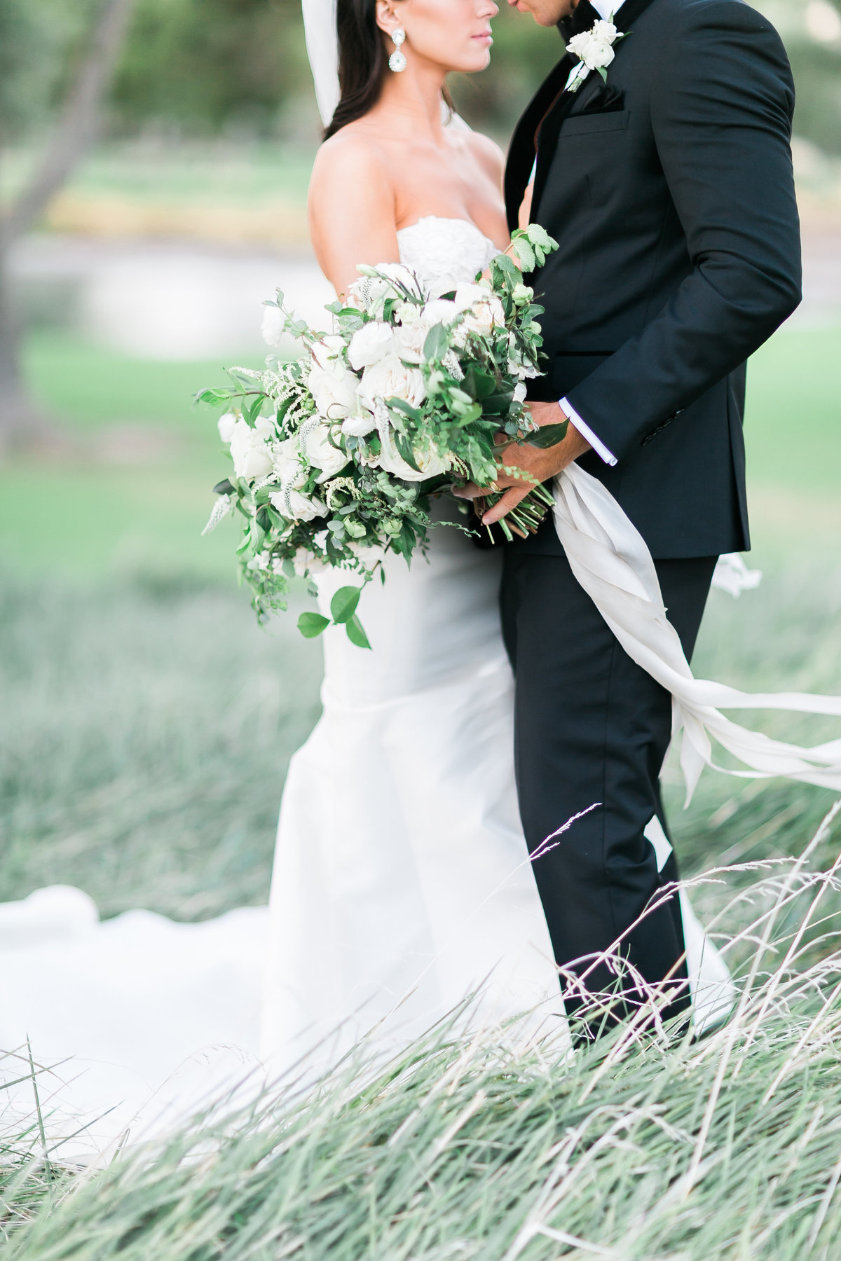bride and groom photo with white floral and greenery bouquet