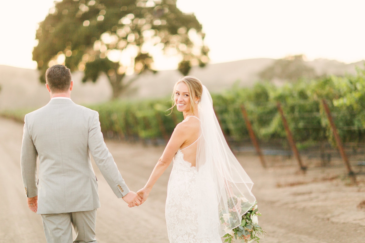 Bride and groom walk through vineyard at Firestone