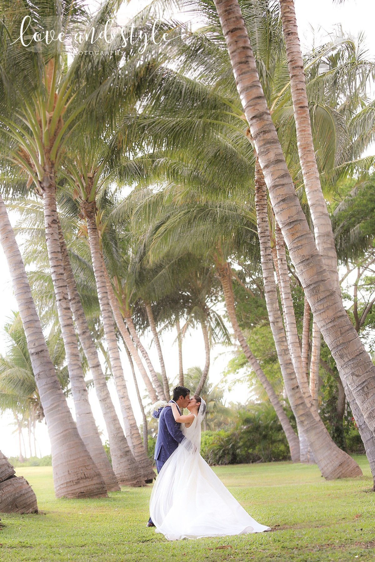 Sarasota-Bradenton Wedding Photography of bride and groom  kissing between palm trees in the rain