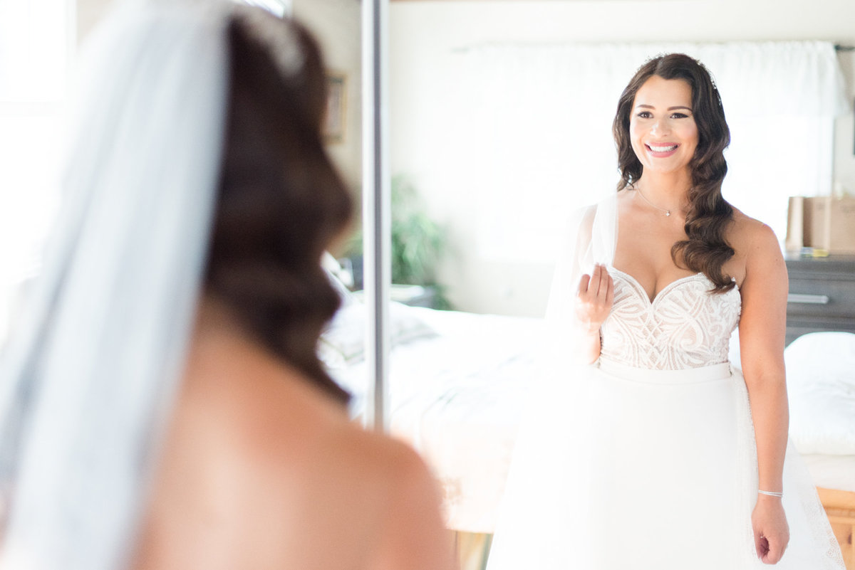 Bride looking in the mirror at her Julie Vino gown before her wedding at The Chanterelle in Thunder Bay