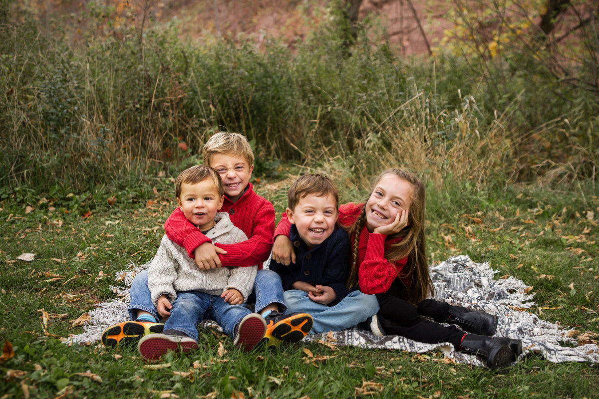 4 children sitting on blanket and smiling outdoors {Milton Family Photographer}