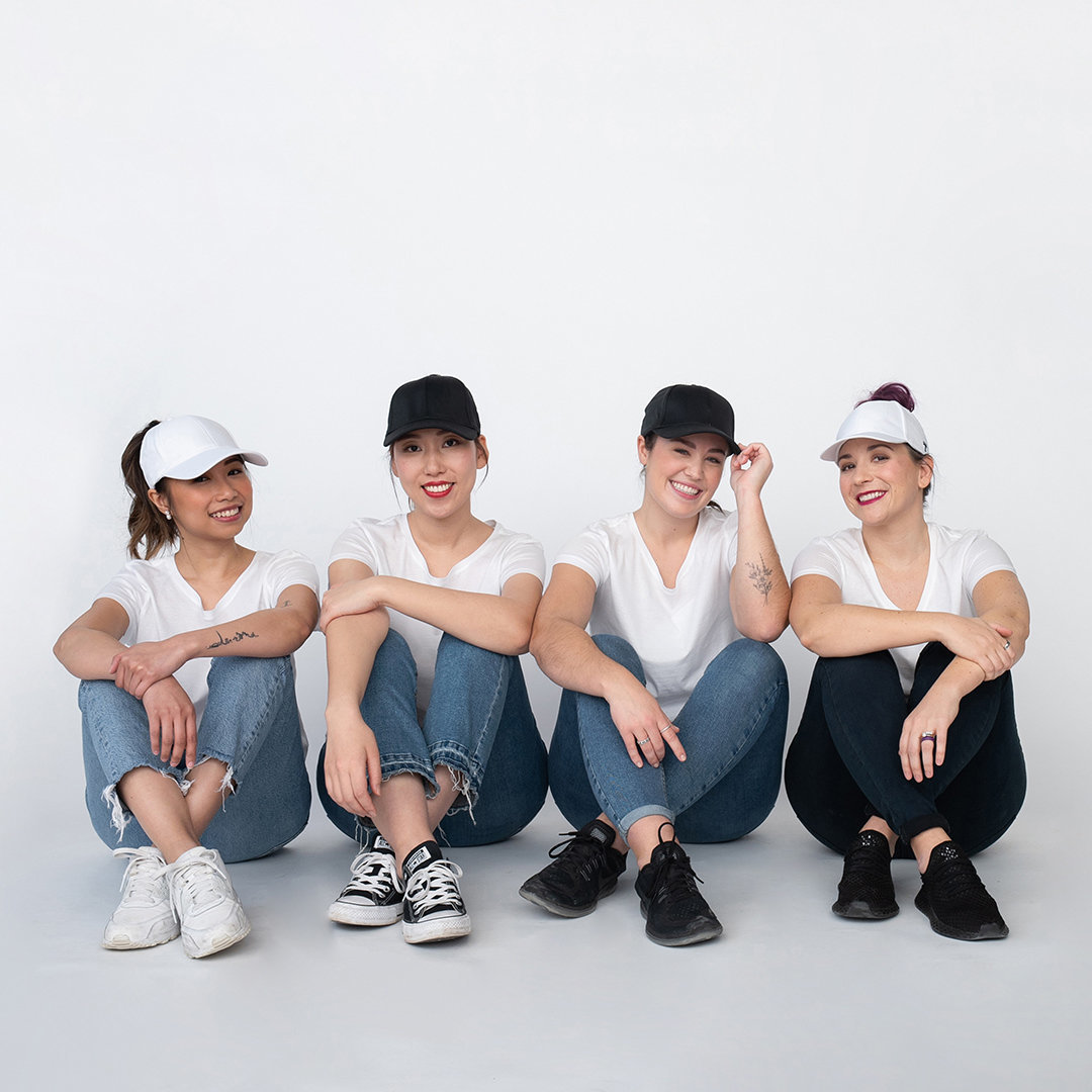 four women sitting on floor modelling baseball hats