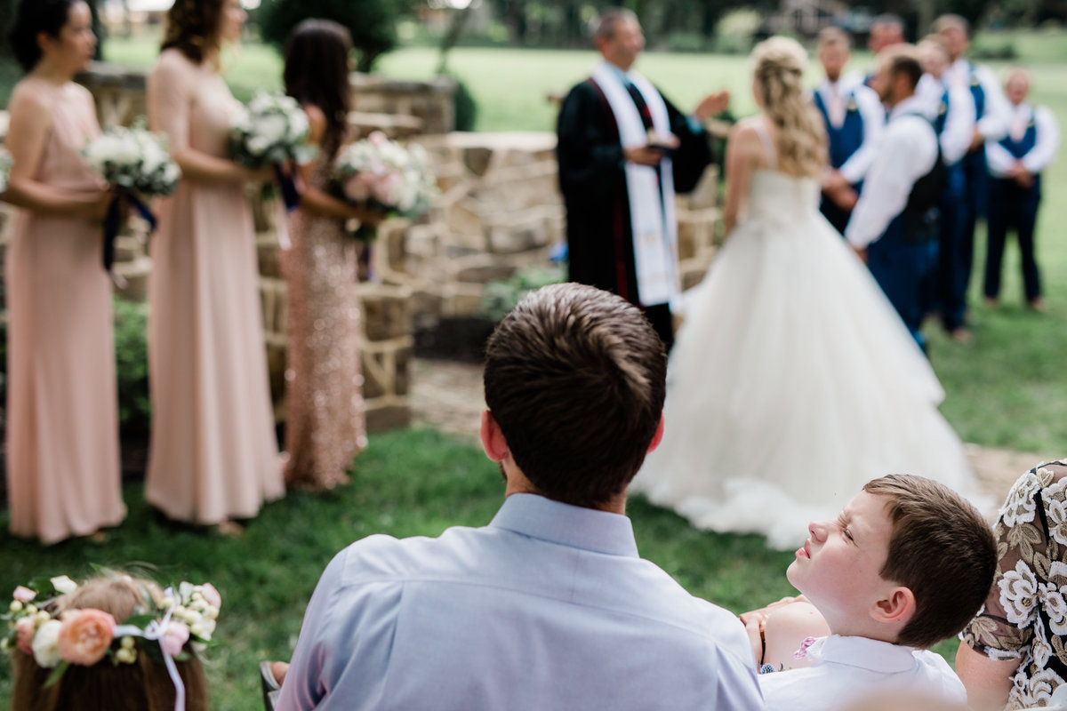Ring bearer boy bored during ceremony at Historic Shady Lane - by Maria Silva Goyo Photography