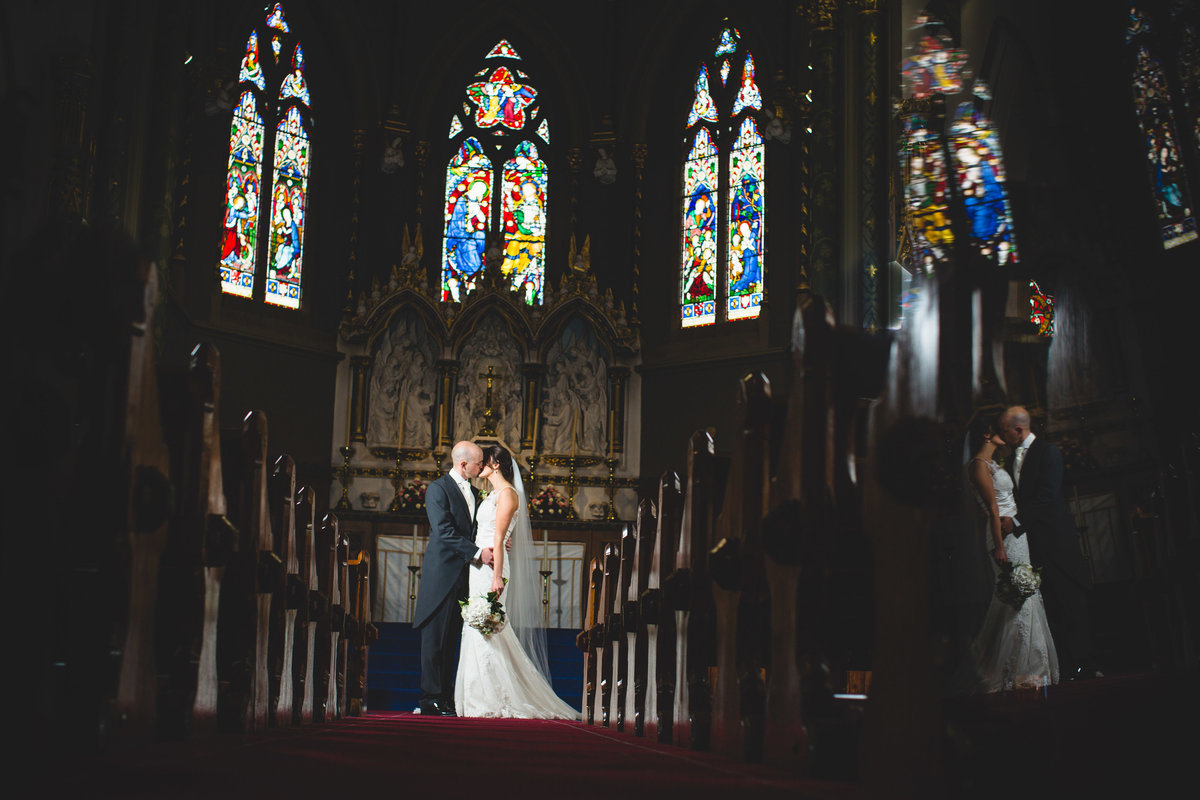 wedding photo of a bride and groom in church with the stained glass window