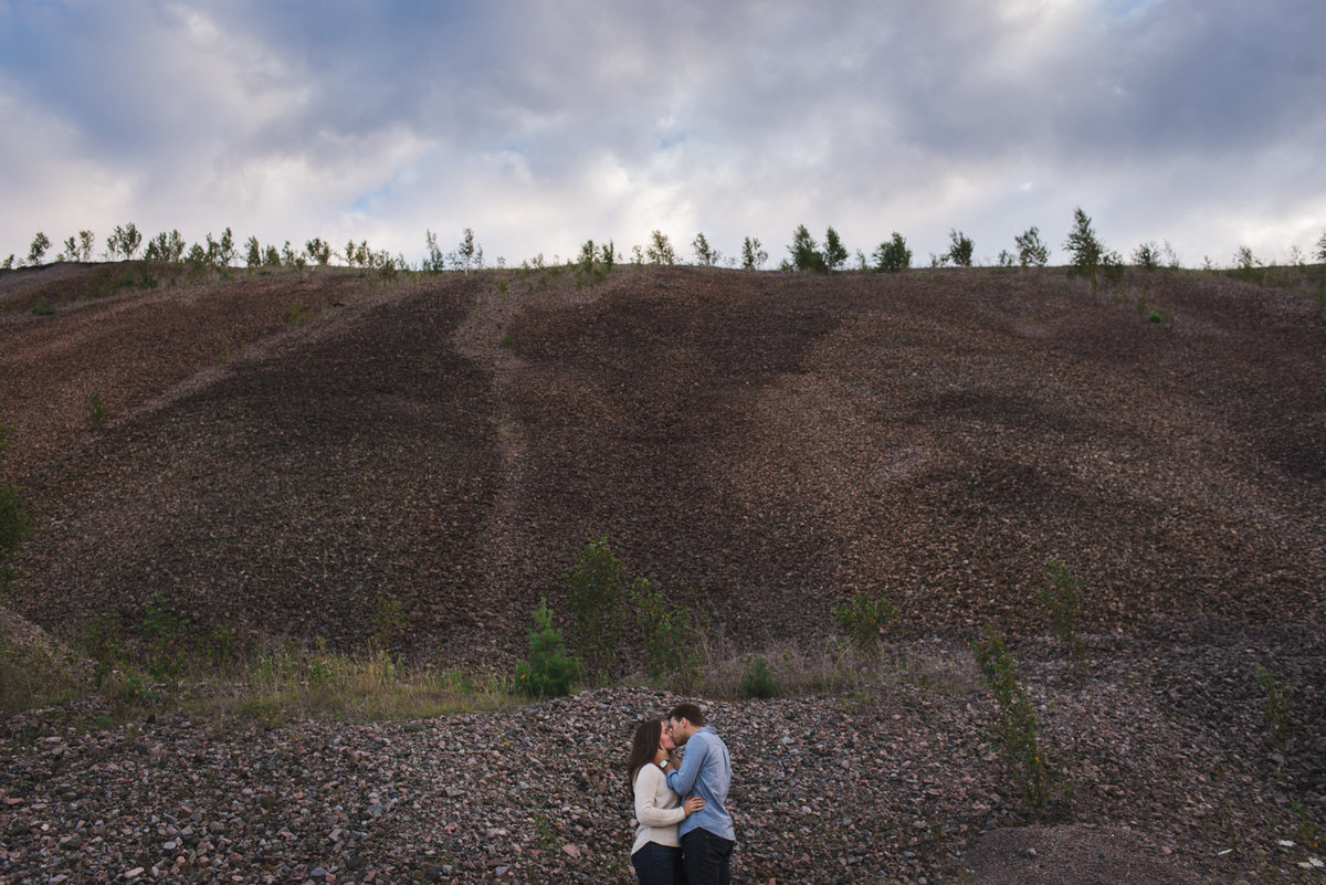 couple cuddling in front of giant gravel pile at old mine