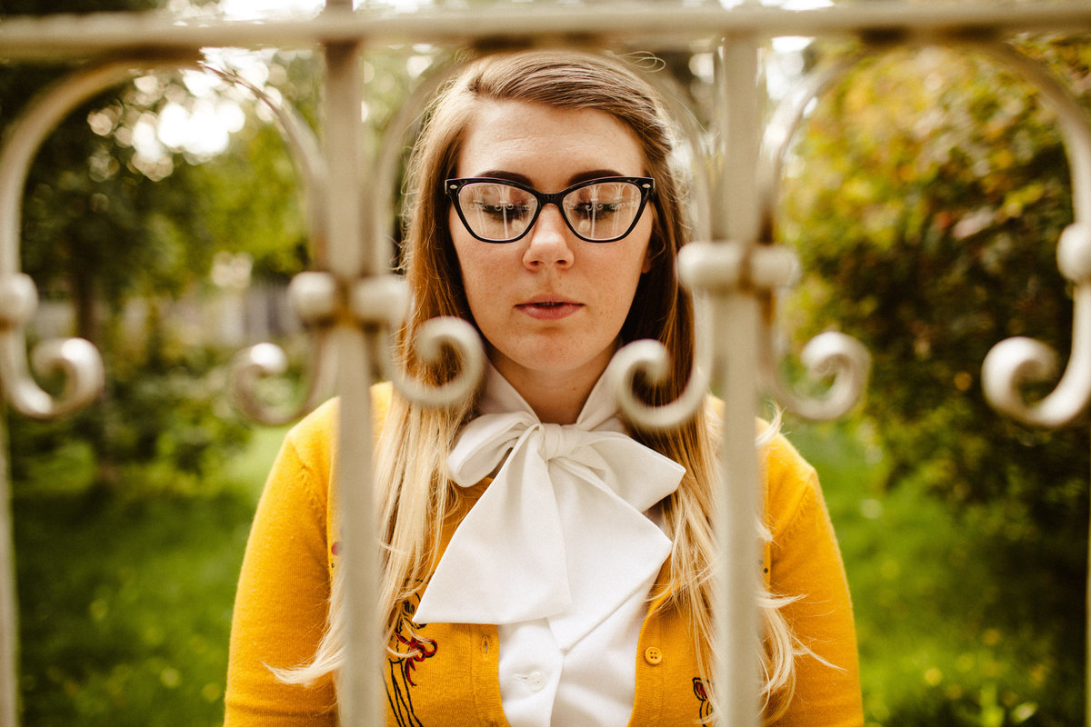 portrait of girl in retro glasses and yellow sweater through a fence