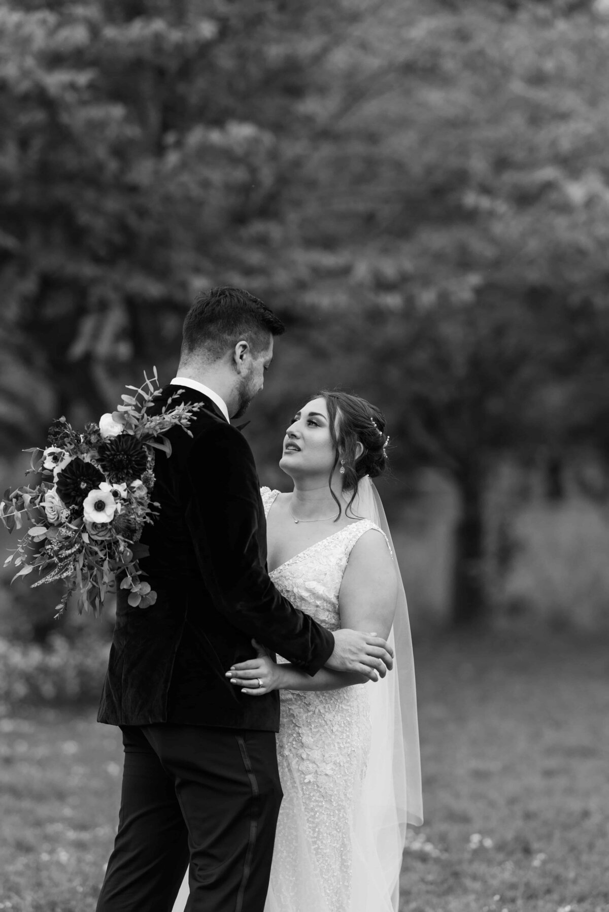 Black and White image of bride and groom looking at one another.