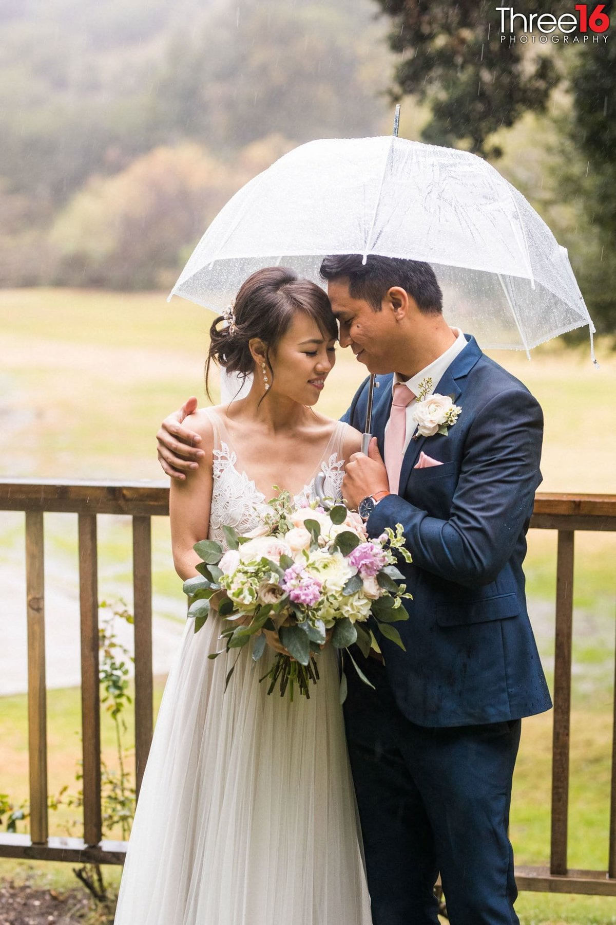 Bride and Groom share a quiet moment together under an umbrella due to rain