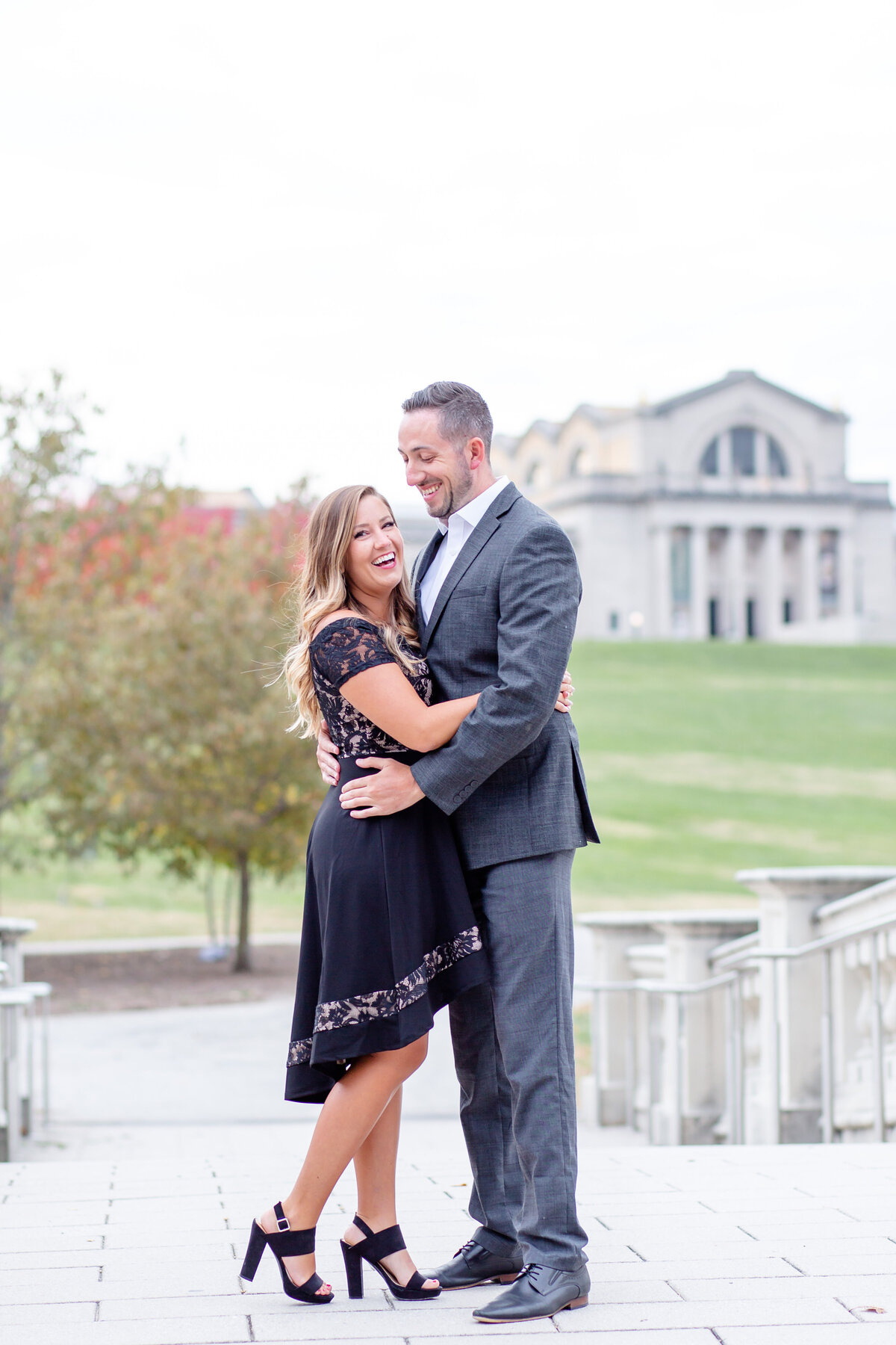 Fall Sunset Engagement  Session with black dress couple laughing on bridge at the bottom of Art Hill  in Forest Park in St. Louis by Amy Britton Photography Photographer in St. Louis