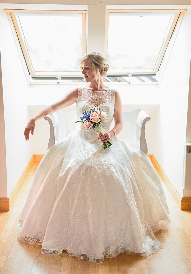 blonde bride wearing an a-line, sweetheart neckline dress sitting on a white seat under window light while holding a pink and purple wedding bouquet