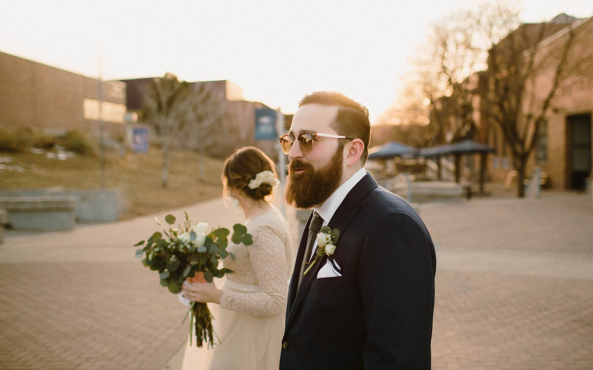 A bride and groom walk in the sunset, the bride holding a bouquet and looking towards the sky, the groom looking ahead and wearing sunglasses