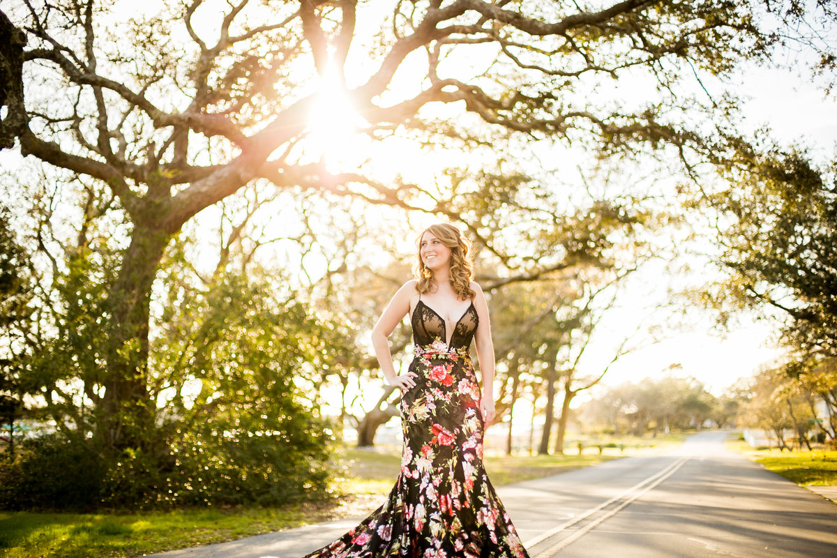 Teenage girl poses in her prom dress in the middle of the street under trees during senior portrait session