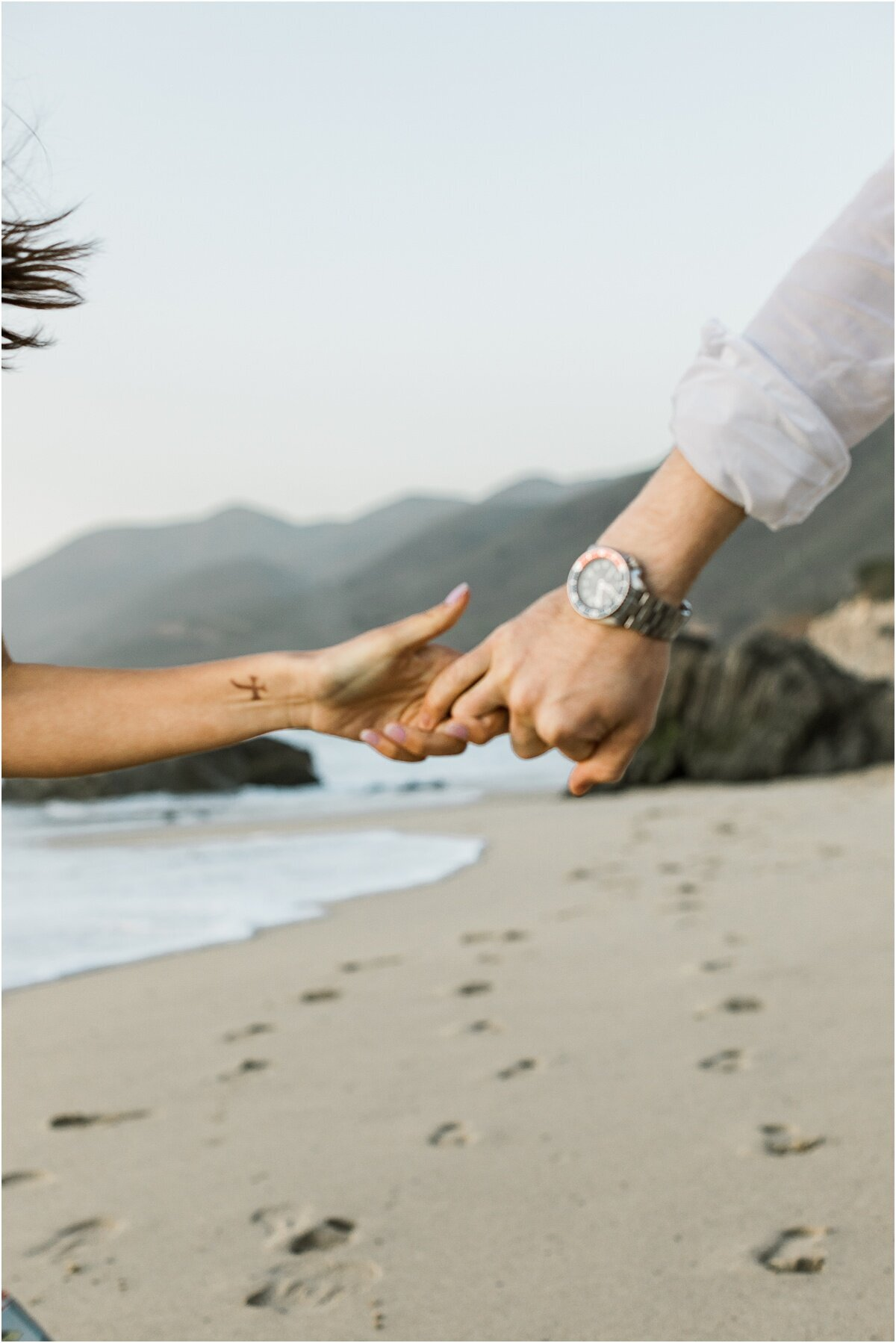 engagement session of couple running on big sur beach