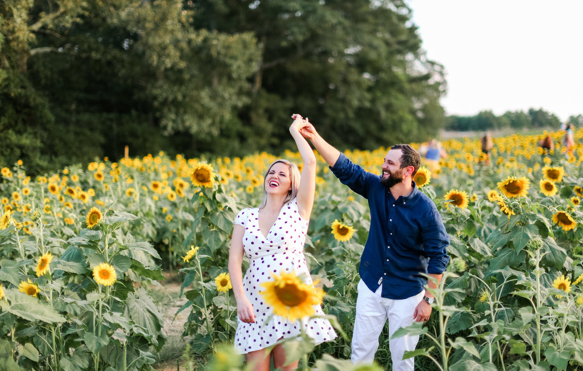 Engaged couple dances in sunflower field