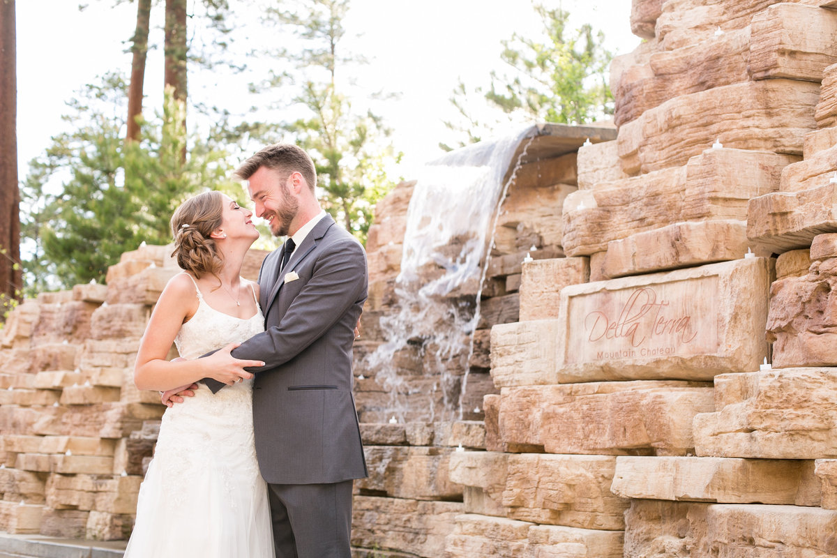 bride and groom in front of waterfall at Della Terra
