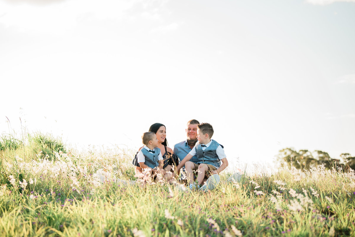 family-sitting-in-long-grassy-field-at-sunset-lead-images-2