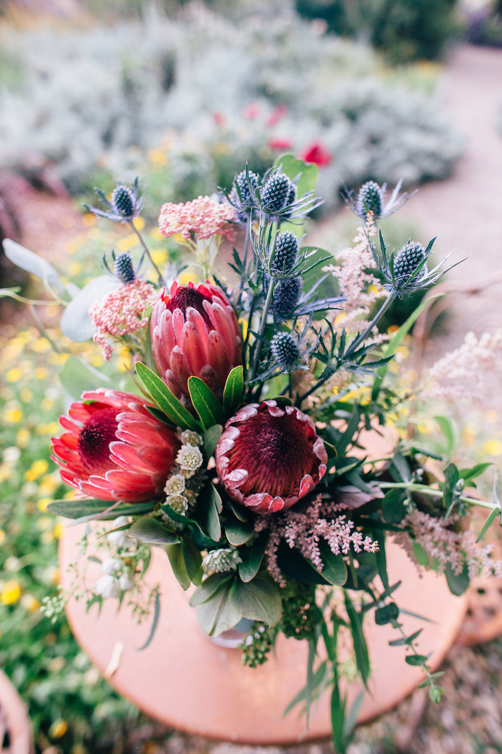 desert inspired wedding floral arrangement with pink protea flowers