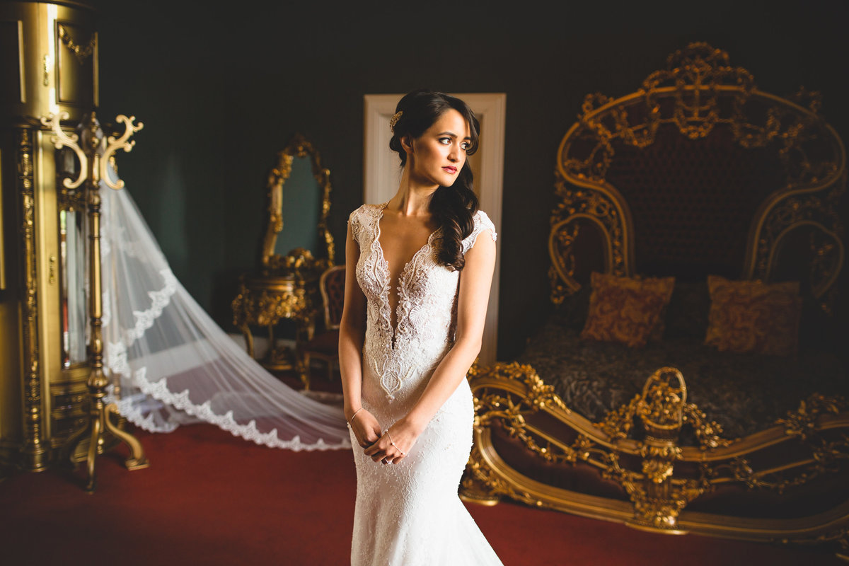 bride in lace wedding dress low cut in grand bedroom with gold bed photographed in window light