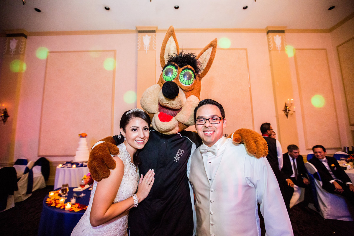 bride and groom pose with San Antonio Spurs coyote at wedding reception at Sheraton Gunter Hotel down town