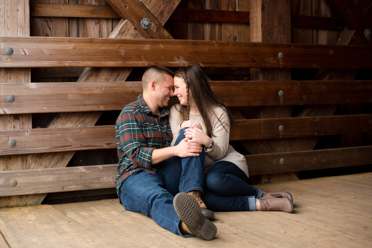 engaged couple poses in rustic bridge for Atlanta wedding photographer