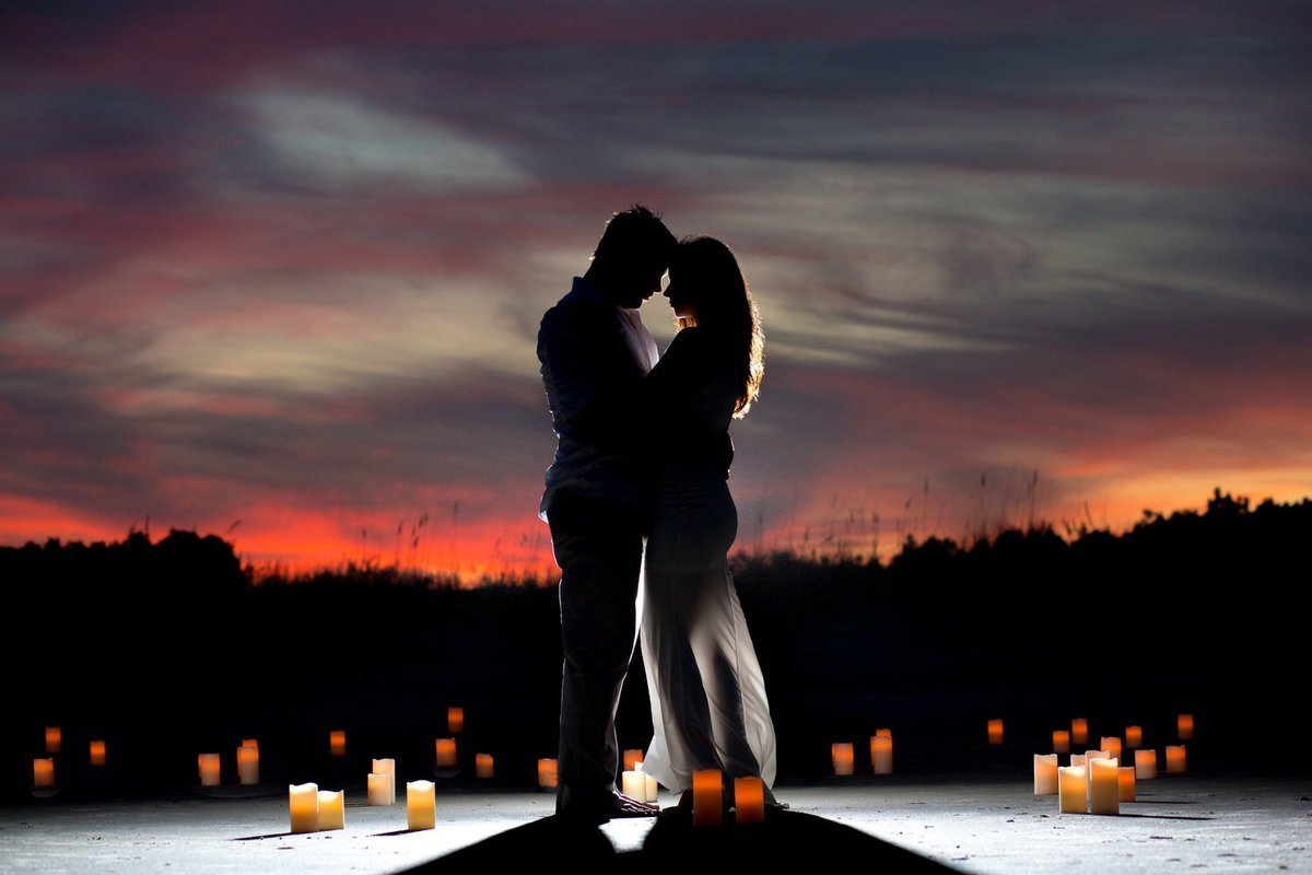 silhouette of couple at sunset with candllelight