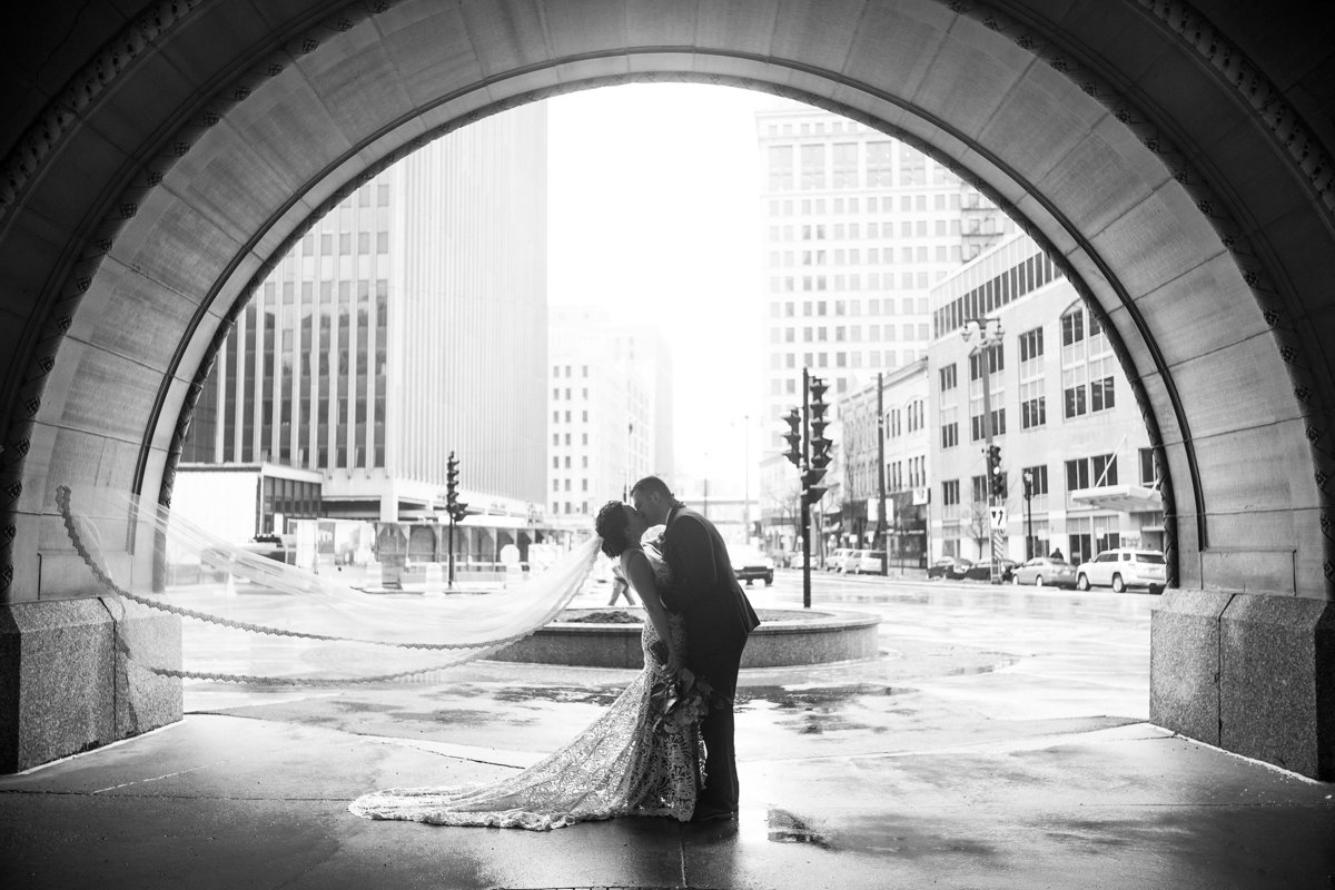 Wedding couple kissing under arch in milwaukee wisconsin