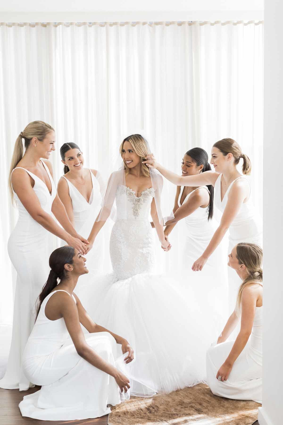 A beautiful and happy bride surrounded by her maids