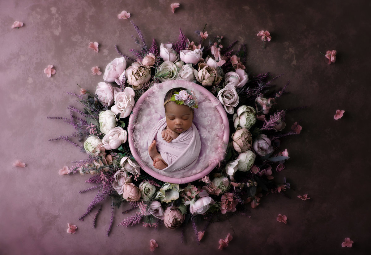 Baby girl in a bowl with purple flowers