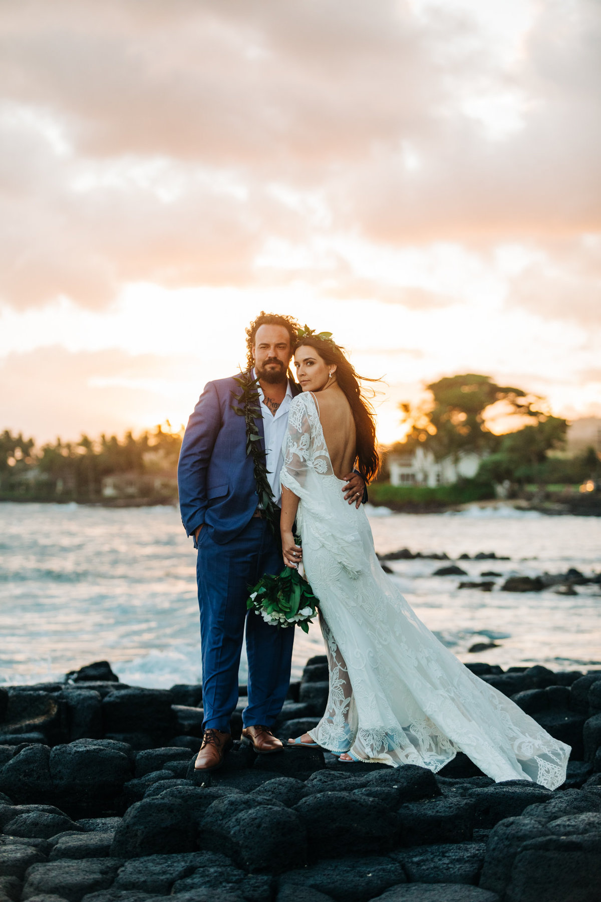 bride in lace dress and groom on rocks over the ocean looking out at sunset