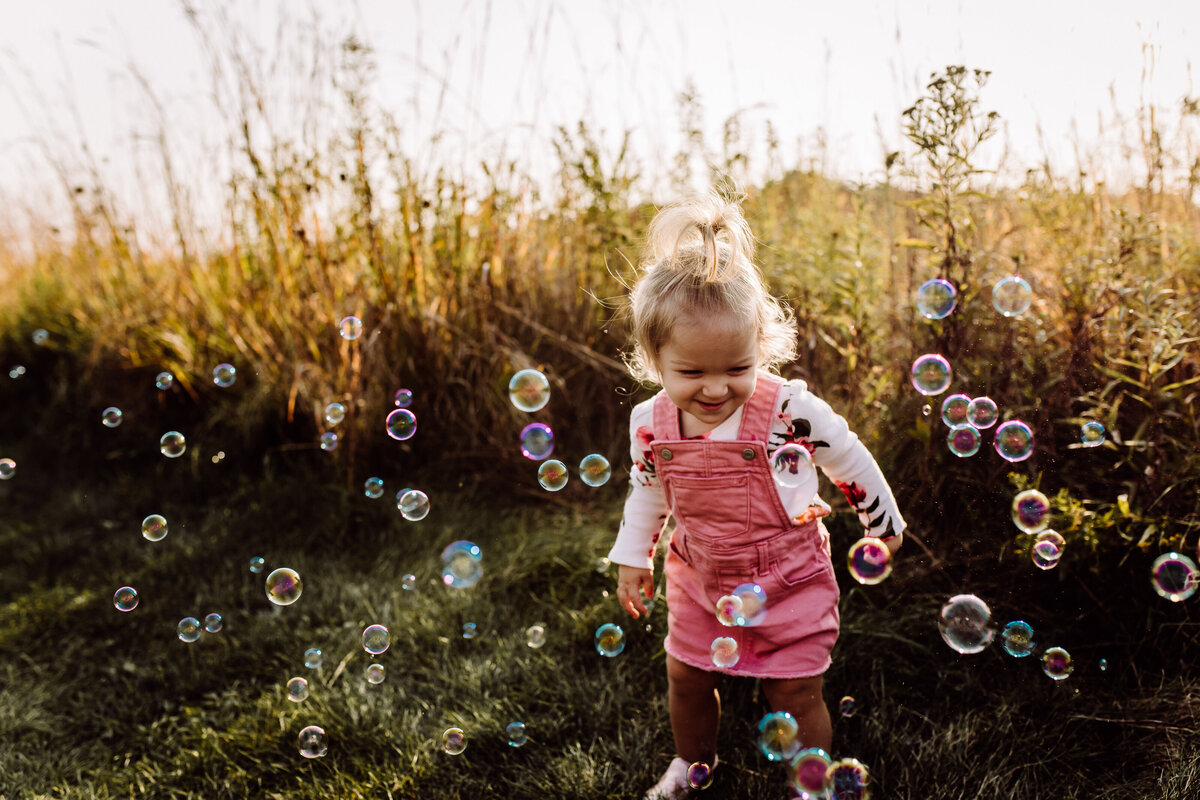 little girl playing in bubbles