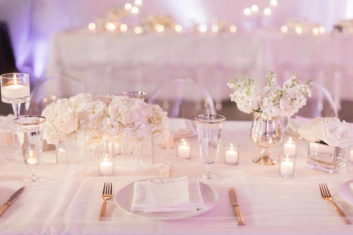 All white candlelit wedding reception table with low arrangements of  stock and hydrangea