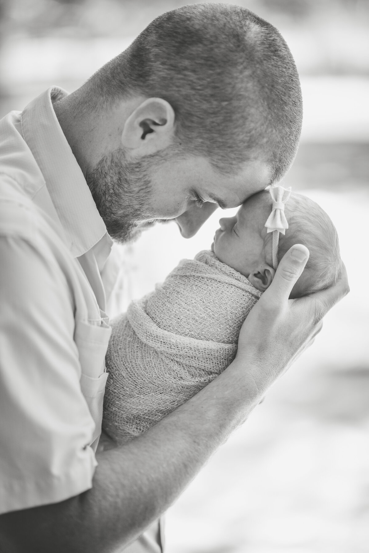 Beautiful lifestyle newborn photography: Black and white of new dad holding newborn girl forehead to forehead in Mississippi