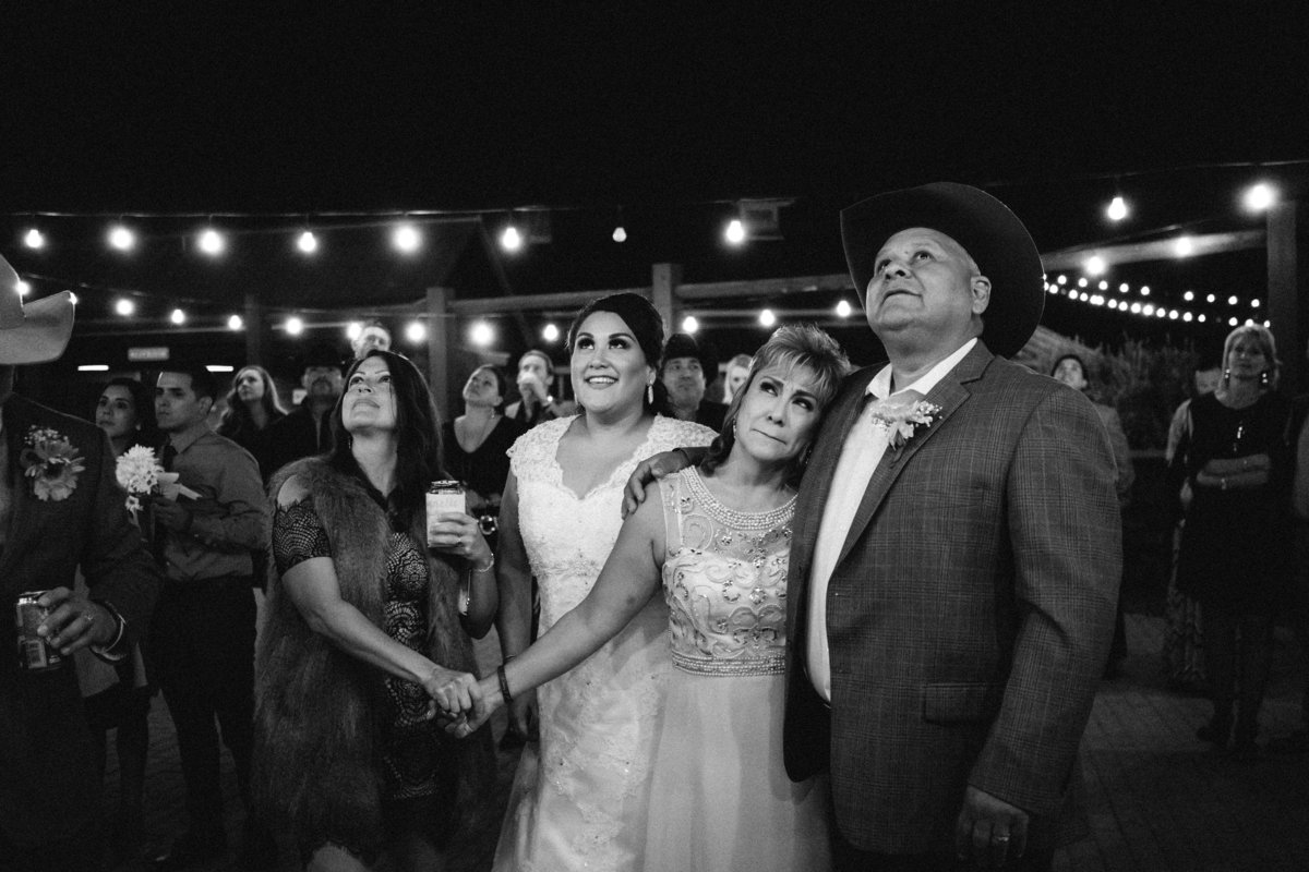 bride looking into sky holding hands with guests for moment of silence at wedding at The Grande Hall at Hoffman Ranch
