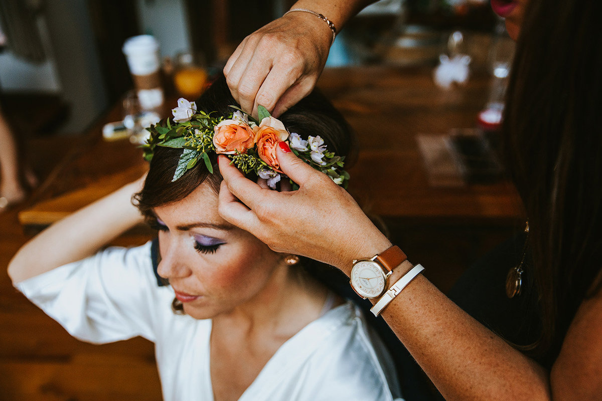 a bride getting a flower crown put on