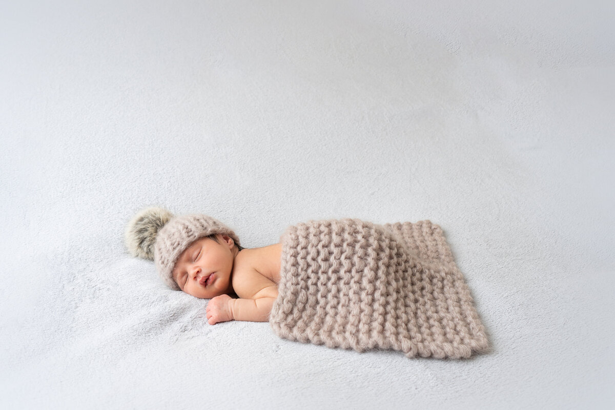 newborn-baby-in-fluffy-hat-posing-on-white-backdrop