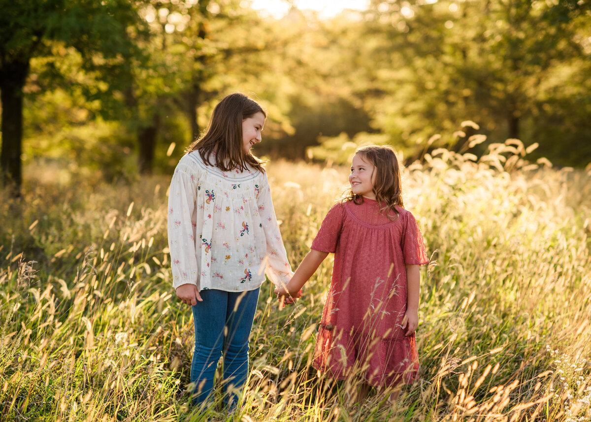 Des-Moines-Iowa-Family-Photographer-Theresa-Schumacher-Photography-Golden-Hour-Grass-Sisters-Holding-Hands