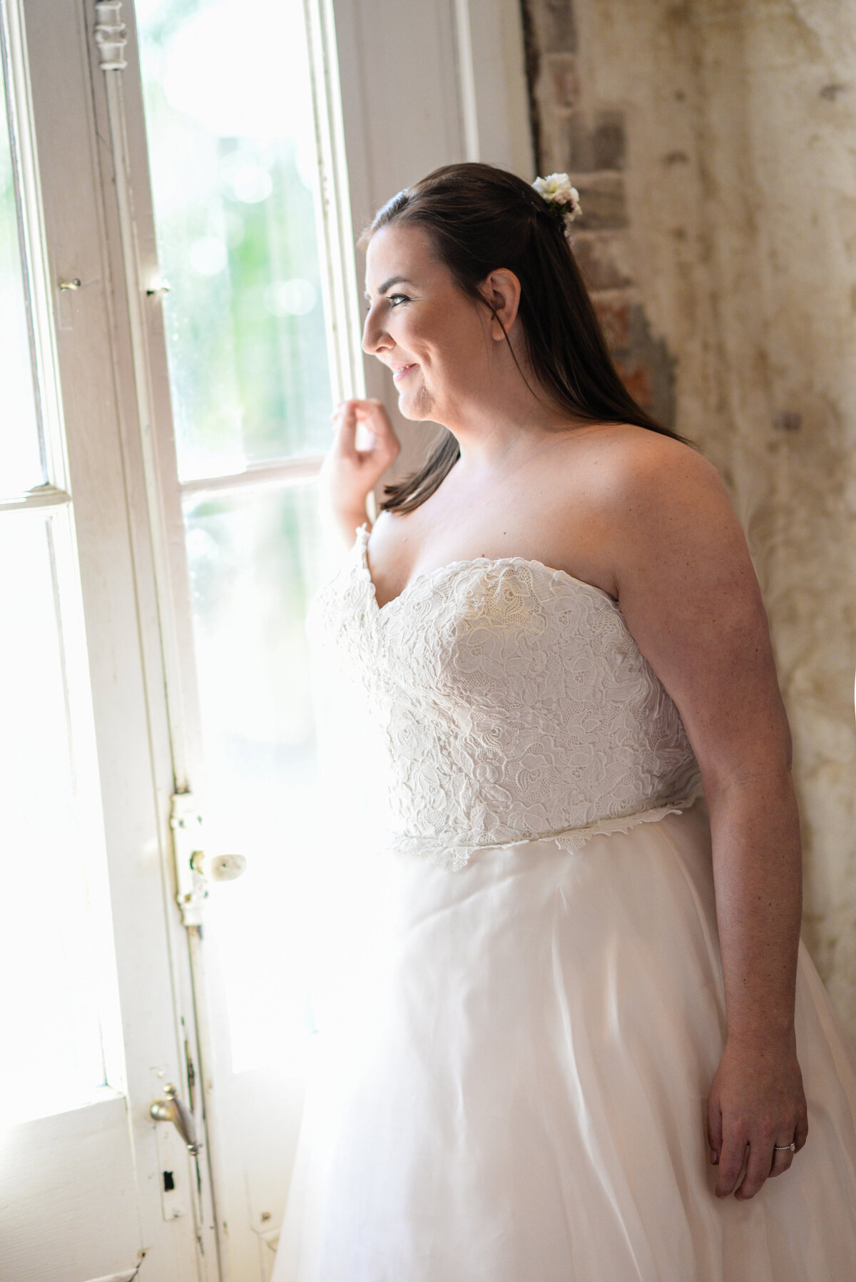Beautiful bridal portrait photography: bride gazes out a window at Race & Religious in New Orleans, Nola Wedding Photographer