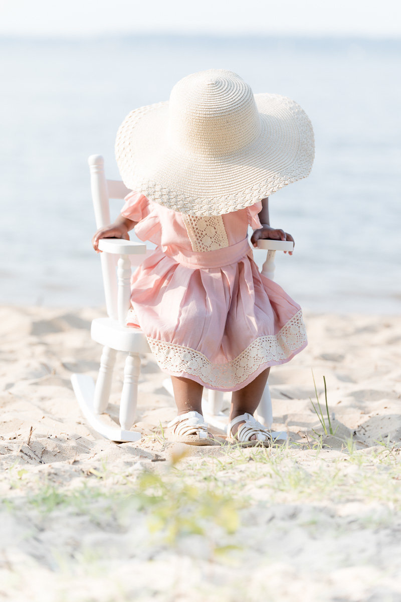 Toddler in pink dress sits on white rocking chair with big sun hat covering face