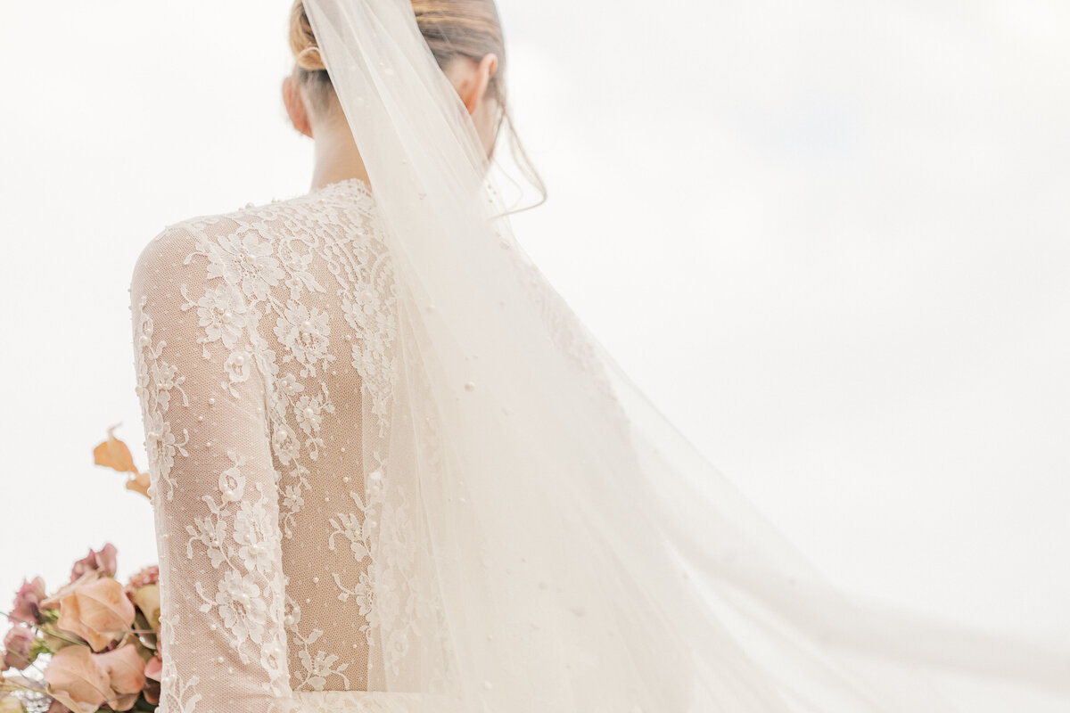 View of a bride from behind with her veil trailing in the breeze while wearing wedding gown with long sleeved lace bodice