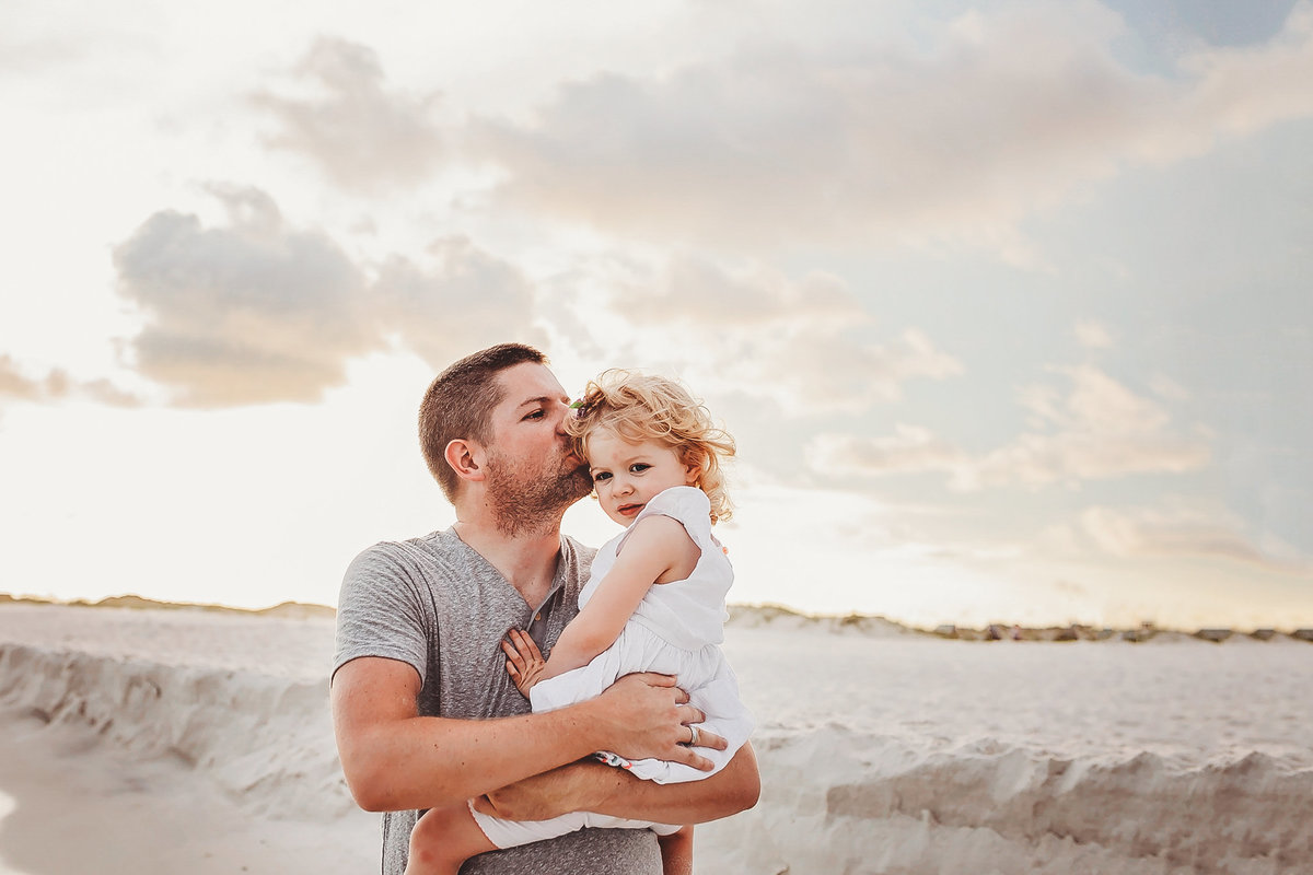 Dad kissing daughter on head, at beach