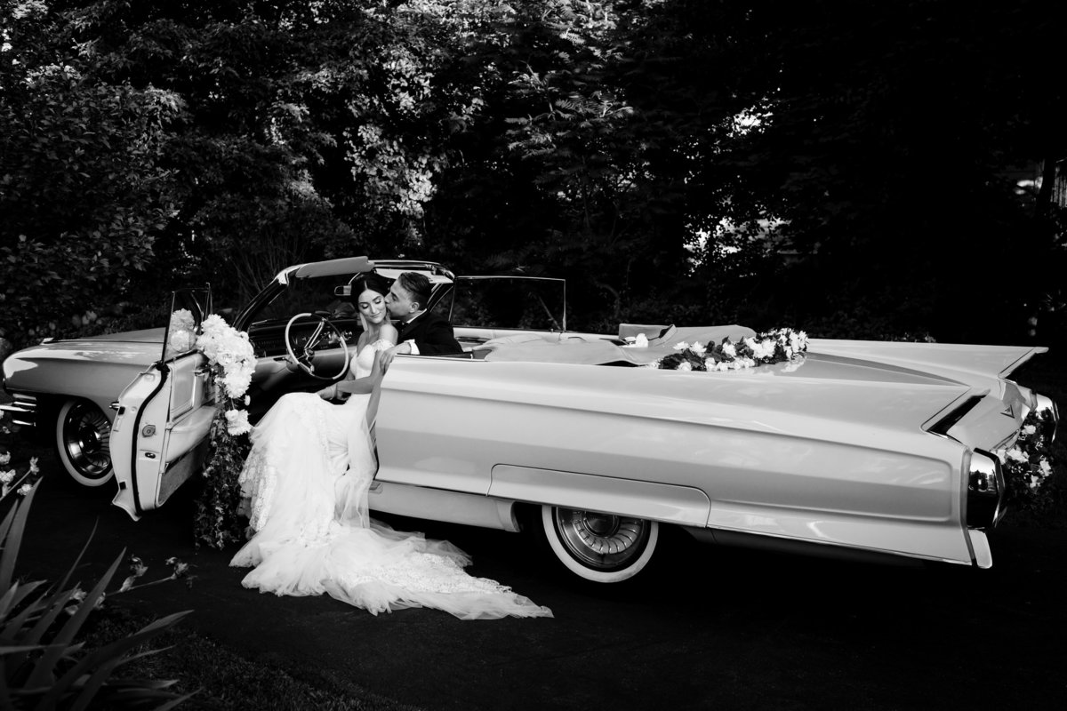 Peabody Essex Museum wedding the bride and groom sit close together in a vintage car after their Greek Orthodox ceremony in Boston