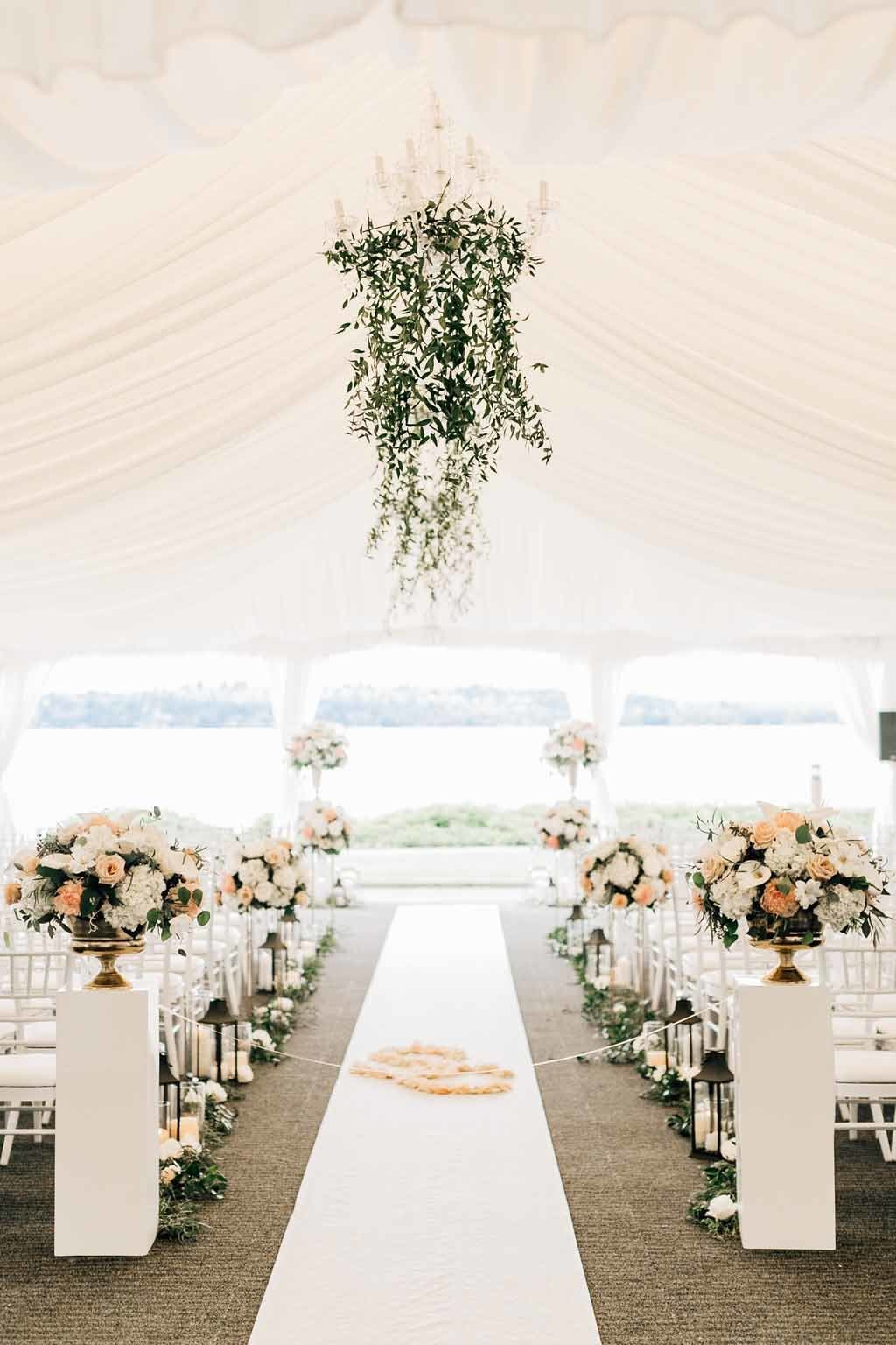 Beautiful Tent wedding in Seattle with tall floral lining the aisle and greenery covering the chandeliers at Woodmark Hotel.