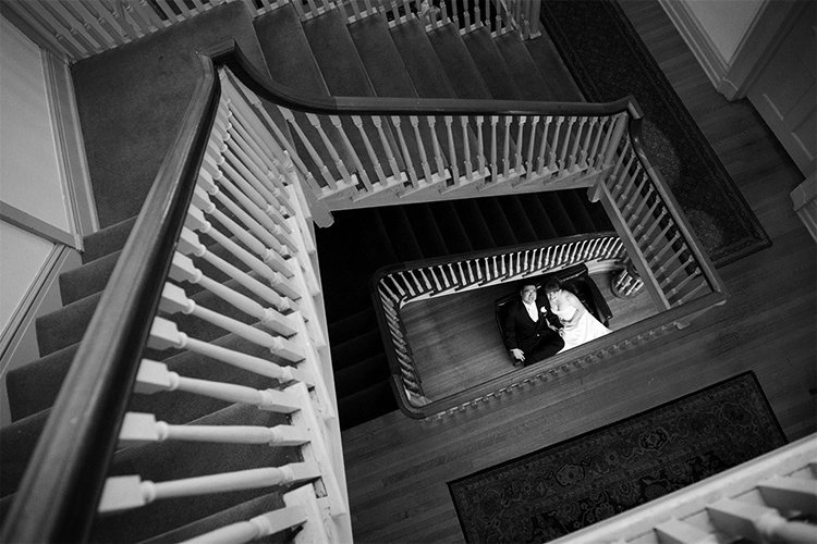 A shot from above of a bride and groom at the bottom of the winding staircase at the University and Whist Club in Wilmington Delaware